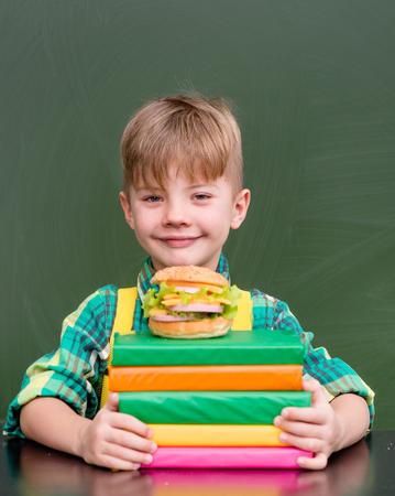 niños comiendo: El muchacho joven con los libros y la hamburguesa.