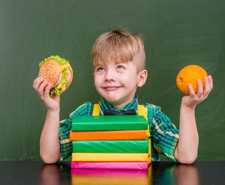 niños comiendo: Pensativo muchacho con naranja y hamburguesa. Foto de archivo