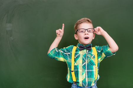 Surprised boy stands near empty chalkboard and showing finger up. Stockfoto