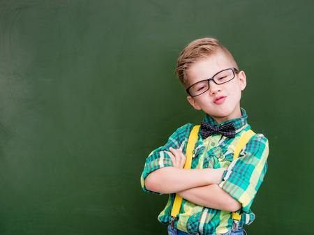 nerd: Funny happy nerd near empty green chalkboard