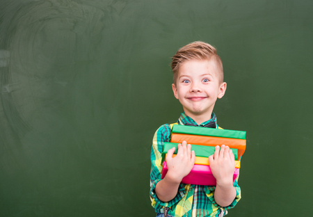 looking to camera: Happy boy with books near empty green chalkboard. Stock Photo