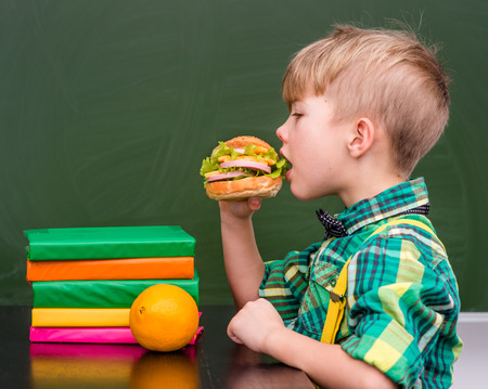 lunchtime: Young student eating a sandwich at lunchtime. Stock Photo