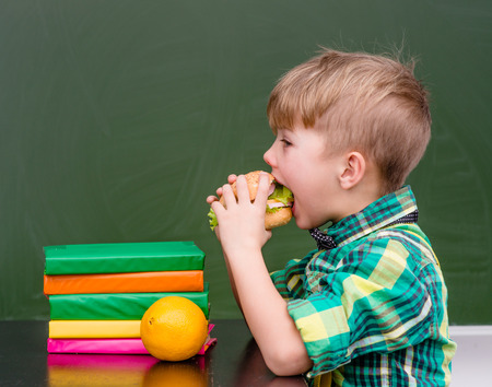 elementary: Young schoolboy eating hamburger.