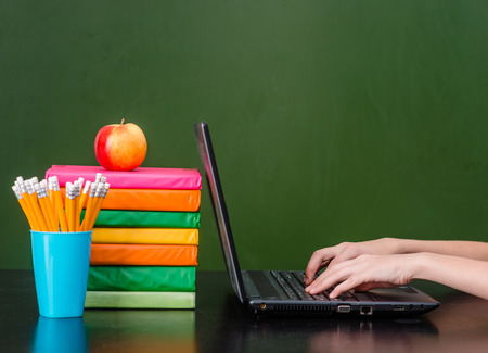 students in classroom: Hands typing on notebook near empty green chalkboard. Stock Photo