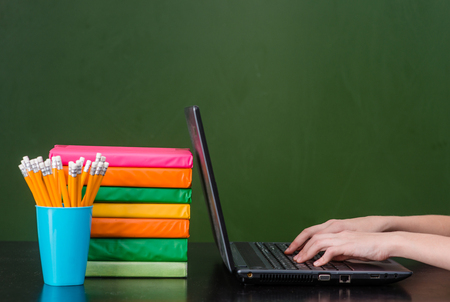 chalk board: Hands typing on notebook in classroom. Stock Photo