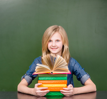 pile of books: Happy girl with pile books near empty green chalkboard. Stock Photo