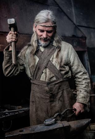 hair man: Blacksmith working in the smithy. Stock Photo