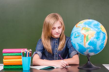 young lady: Teen girl sitting in classroom near empty green chalkboard. Stock Photo