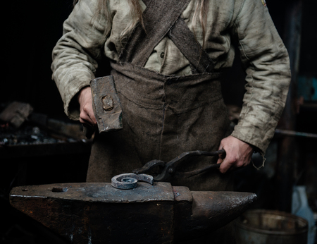 ancient blacksmith: rustic blacksmith forges item on the anvil.