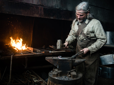 farriery: Gray-haired smith forges detail in the smithy.