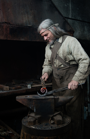 farriery: Old gray blacksmith forges the metal product in the smithy. Stock Photo