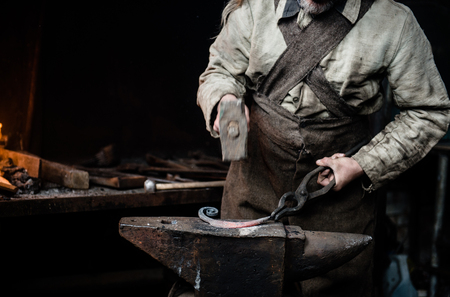 ancient blacksmith: closeup hands of the village smithy, pulling the metallic article. Stock Photo
