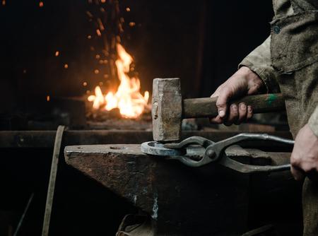 Les mains d'un forgeron au travail dans la forge. Banque d'images - 53820932