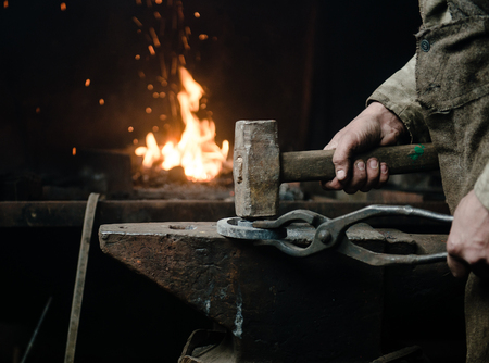 ancient blacksmith: The hands of a blacksmith at work in the smithy.
