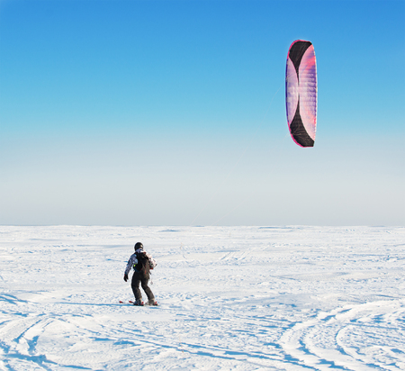 snowkiting: Kite surfer being pulled by his kite across the snow.