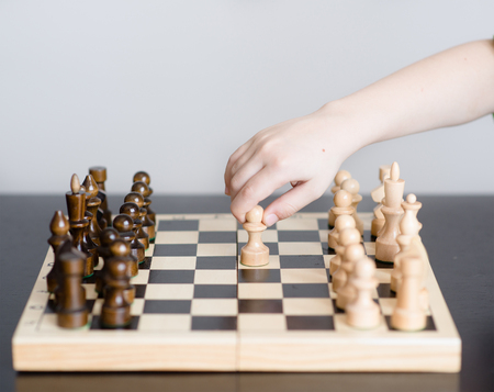 first move: boy plays chess and makes the first move a pawn.