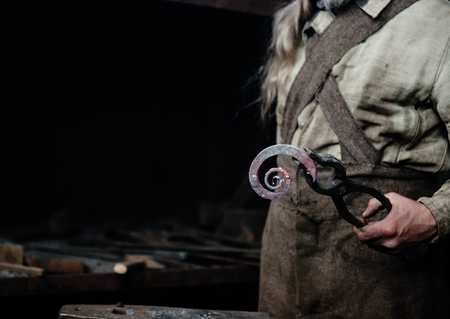 farriery: The hands of a blacksmith holding forged product.
