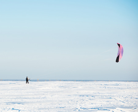 snowkiting: Kiteboarder with kite on the snow.