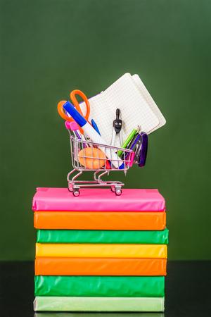 full shopping cart: Full shopping cart standing on books near empty green chalkboard.