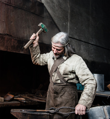 farriery: Blacksmith working in the smithy. Stock Photo