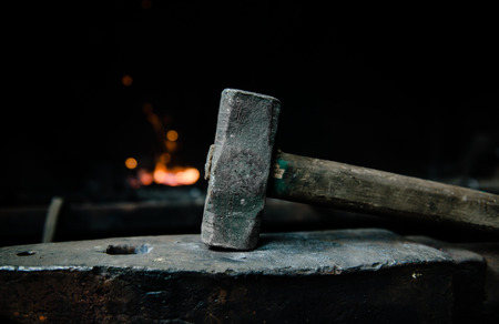 farriery: blacksmith hammer on the anvil against the background of fire.