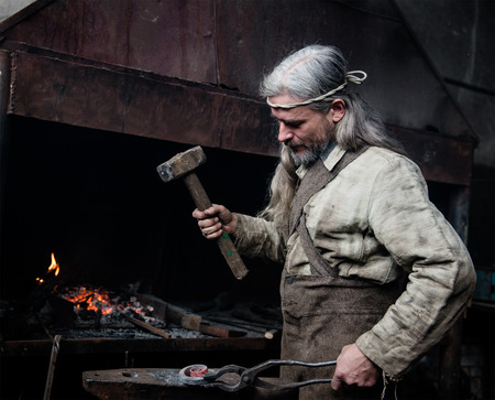 farriery: Old blacksmith forge forges metal products. Stock Photo