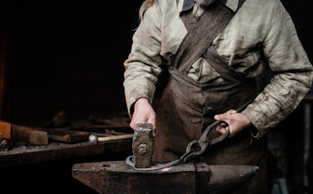 farriery: rustic blacksmith forges item on the anvil.