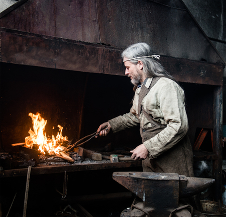farriery: Blacksmith heats item before forging. focused on the fire.