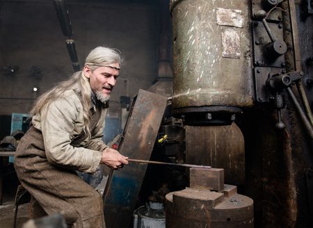farriery: Blacksmith works with a power hammer.