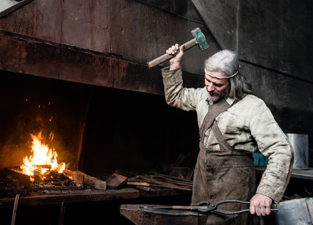 Gray-haired smith forges detail in the smithy.