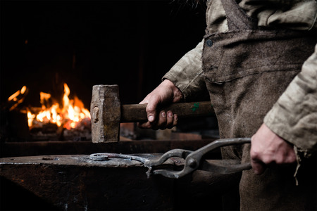 The hands of a blacksmith at work in the smithy.