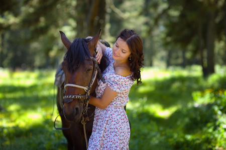 Beautiful woman walking with a horse.
