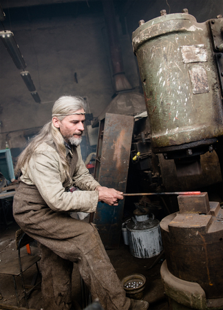 ancient blacksmith: Blacksmith works with a power hammer.