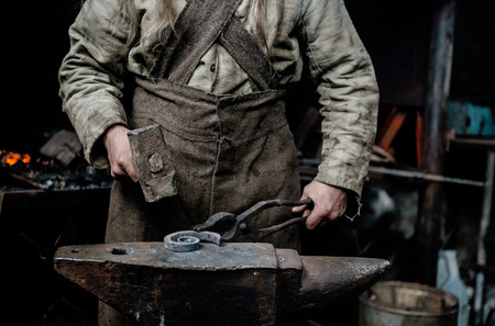 farriery: The hands of a blacksmith at work in the smithy.