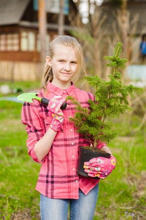 spruce: Teen girl with tree seedling.