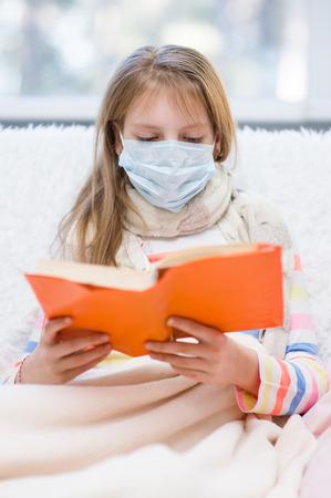 healthcare and medicine: ill little girl in medicine health-care mask reading a book.