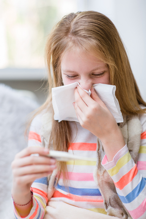 rheum: Young girl blowing her nose and checks the temperature.