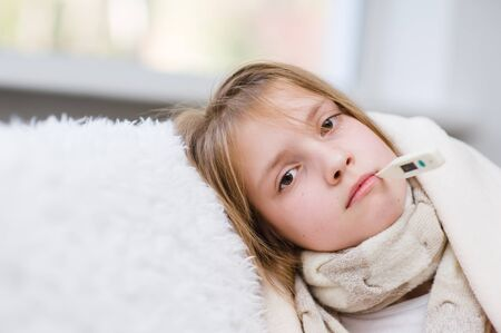 grippe: Sick girl with thermometer in mouth looking at camera. Stock Photo
