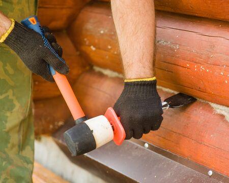caulk: Male hands caulk log walls.