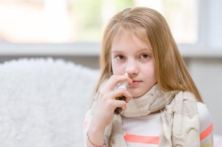 nasal drops: Girl with flu using nose spray.