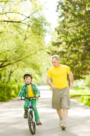 runs: Elderly man runs together with her grandson, who rides a bike. Stock Photo
