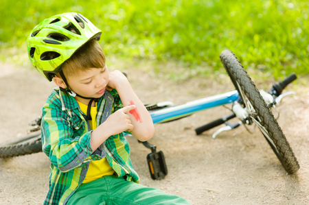 injure: boy fell from the bike in a park.