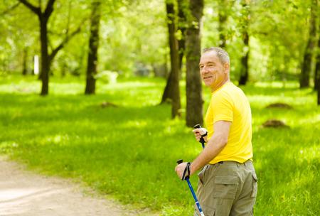 ancianos caminando: Hombre mayor que hace nordic walking en el parque.