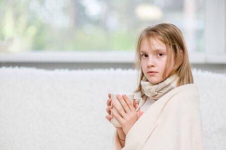 medicate: Diseased girl drinks hot tea. Stock Photo