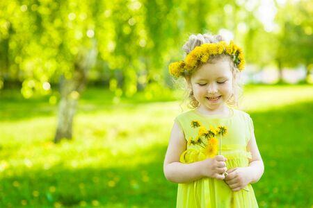 petites fleurs: Girl with dandelions in summer park. Banque d'images