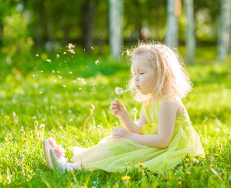 blowing dandelion: Little girl blowing dandelion.