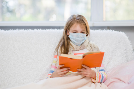protective: ill little girl in medicine health-care mask reading a book.