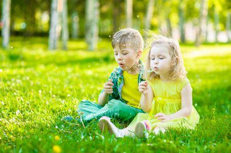 blowing dandelion: Little girl and boy blowing dandelion together.