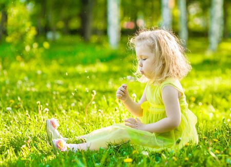 girl blowing: little girl blowing dandelion. Stock Photo