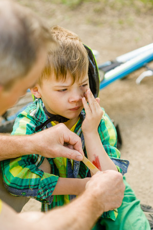bandaid: Grandfather putting band-aid on young boys injury who fell off his bicycle. Stock Photo
